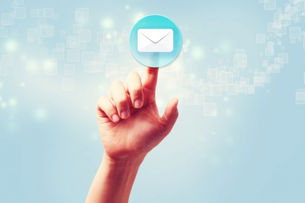 Hand pressing a envelope icon over light blue background