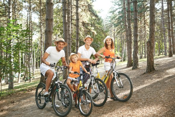 Happy family on bicycles for a walk in summer park.