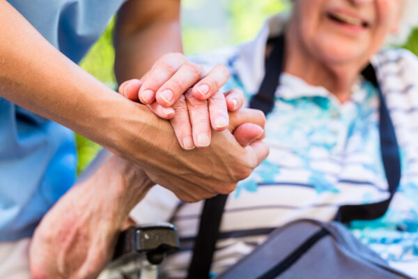 Nurse consoling senior woman holding her hand. LICENZA ADOBE STOCK Opi Bologna